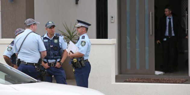 Police attend a property in the suburb of Merrylands in Sydney, Wednesday, Oct. 7, 2015. Police arrested four people during a series of raids Wednesday in connection with the slaying of a civilian police worker, which officials have said they believe was linked to terrorism. (AP Photo/Rick Rycroft)