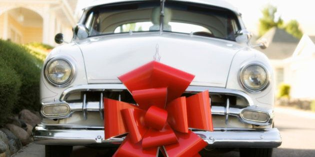 Vintage car with red gift bow attached parked on street outside Victorian style