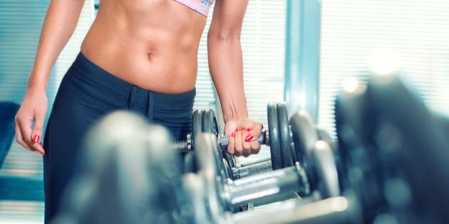 close up of woman holding weight in gym