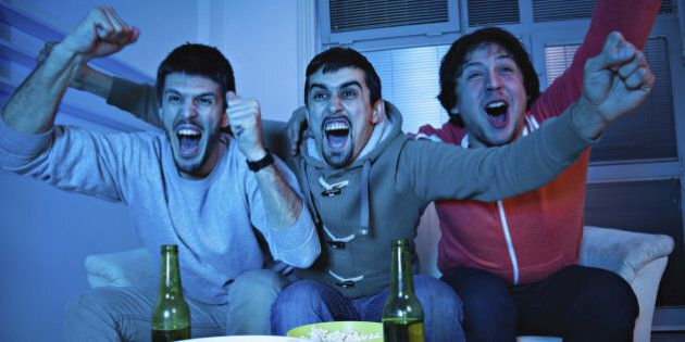 Three young men excited by goal scored during sports
