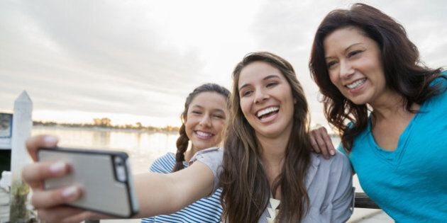 Smiling mother and daughters taking self portrait with smartphone