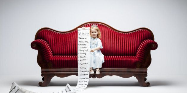 3 year princess girl sitting on red vintage sofa and holding an extraordinary long list of material