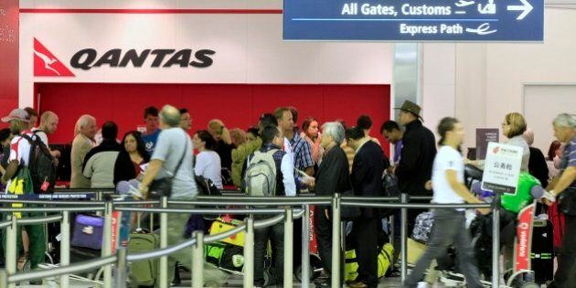 Travelers gather at the Qantas sales desk at Sydney Airport in Sydney, Saturday, Oct. 29, 2011. Qantas...