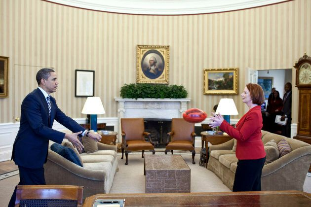 U.S. President Barack Obama practices passing a football with Prime Minister Julia Gillard in the Oval...