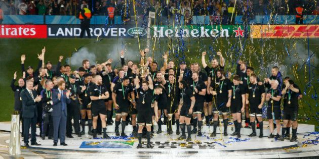 New Zealand All Blacks captain Richie McCaw holds the Webb Ellis trophy aloft as his teammates celebrate...