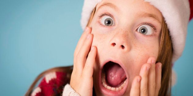 Color image of a little girl with a stressed/shocked/surprised look on her face. She is wearing a Santa...