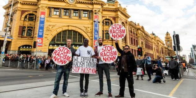 Protestors holding 'Stop racism now' placards stand in front of Flinders Street station during a rally...