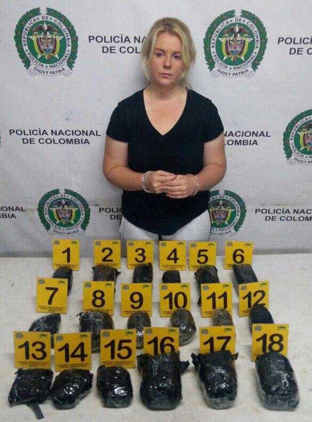 A shell-shocked looking Cassie Sainsbury in handcuffs after her arrest at the international airport in...