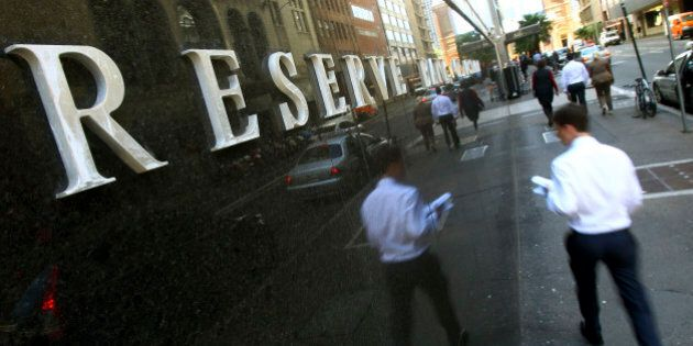 People walk past the Reserve Bank of Australia building in Sydney, Tuesday, Dec. 4, 2012. The Reserve...