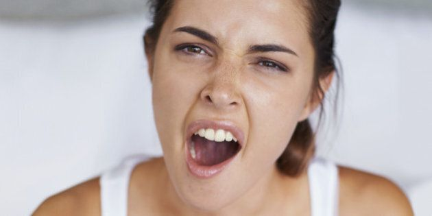 Shot of a young woman giving a big yawn while sitting with a cup of coffee in