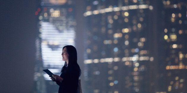 Joyful businesswoman looking away city skyline while using digital tablet, standing against illuminated...