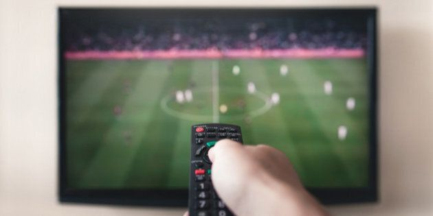 Human hand holding remote control with soccer channel on the television