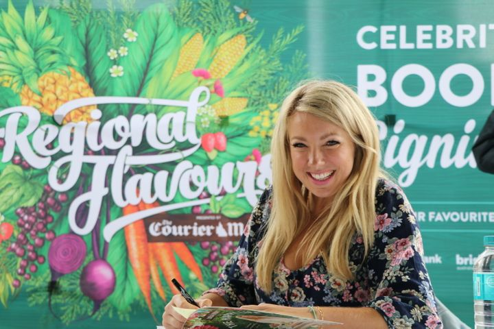 Nutritionist Lola Berry signing her cookbooks after a cooking demonstration.