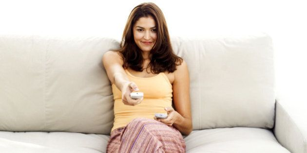 portrait of a young woman sitting on a couch watching television