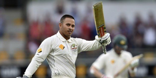 Australia's batsman Usman Khawaja celebrates his first Test century during day one of the first Test...
