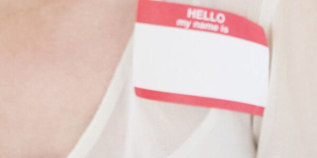 Woman wearing name tag, smiling