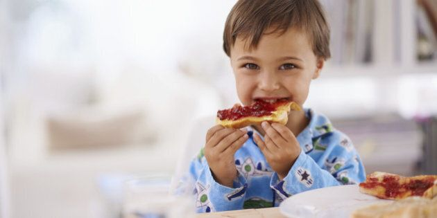 A cute little boy eating toast with