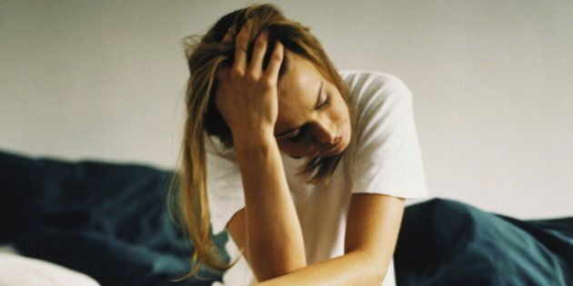 Young woman sitting on edge of bed, holding head in