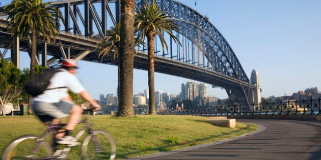 Australia, New South Wales, Sydney. An early morning cyclist rounds Daves Point Reserve at the foot of...