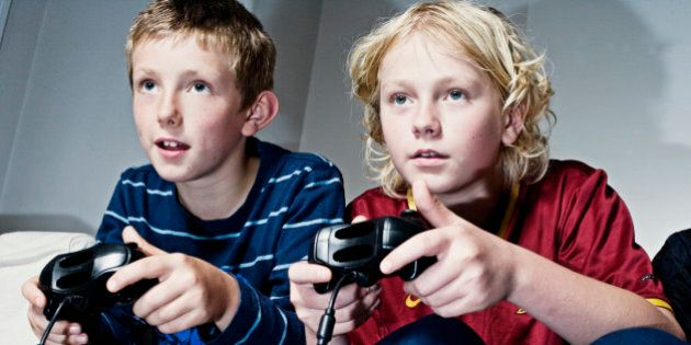 two boys aged 10 and 13 playing with games consoles.