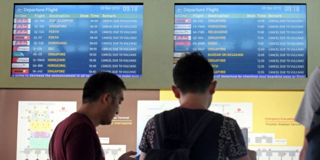Passengers look at a flight information monitor with canceled flights at Ngurah Rai International Airport in Bali, Indonesia, Thursday, Nov. 5, 2015. Thousands of tourists are stranded on three Indonesian islands after ash from the Mount Rinjani volcano forced the closure of airports and blanketed villages and farmlands. (AP Photo/Firdia Lisnawati)