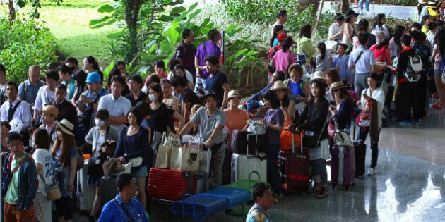 Passengers line up after their flights were canceled at Bali's international airport, in Denpasar, Indonesia,...