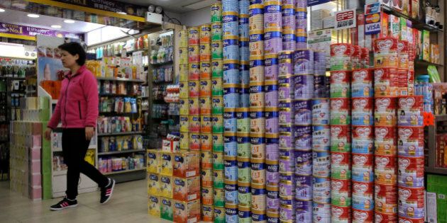 In this Friday, April 10, 2015 photo, a woman walks past cans of baby formula stacked in a shop at a district regarded as a hub of