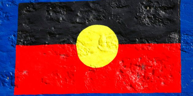 Aboriginal flag painted on stone wall. Official flag of indigenous people of Australia Aborigines also...