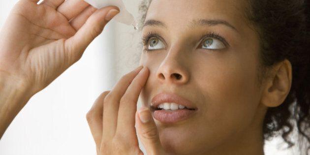 Young woman putting eye