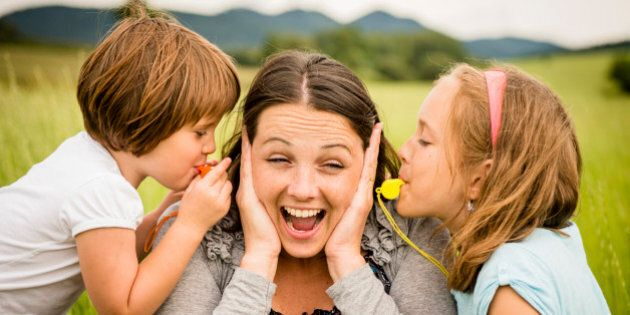 Children blowing whistles to mother's ears- outdoor in
