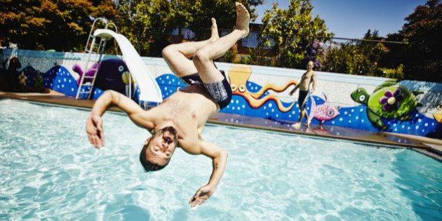Man doing backflip into outdoor swimming pool on summer afternoon with friend watching in
