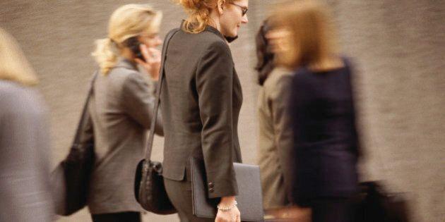 Woman talking on cellular phone, walking in crowd of