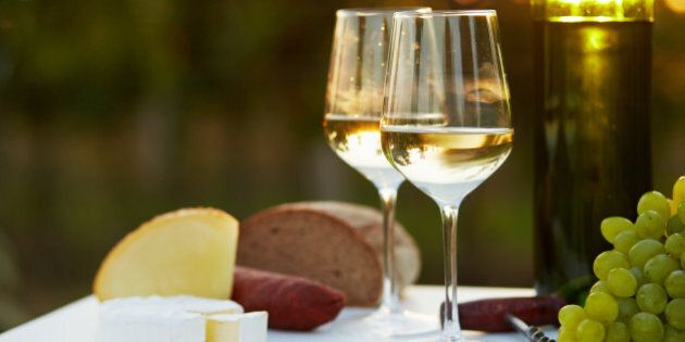 Two glasses of white wine with food at sunset