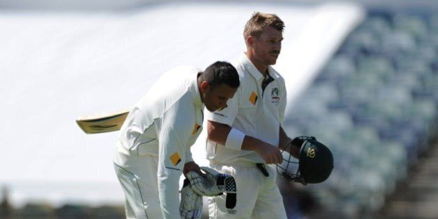 Australia's David Warner (R) and teammate Usman Khawaja (L) take a drinks break on the first day of the...