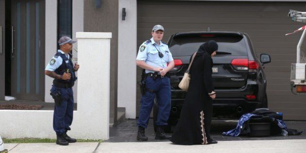 Police talk to a woman outside a property in the suburb of Merrylands in Sydney, Wednesday, Oct. 7, 2015....