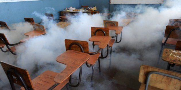 Health ministry personnel fumigate a classroom against the Aedes aegypti mosquito, vector of the dengue,...