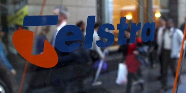 Business people walk through the foyer of Telstra Corp.'s head office in Sydney, Australia, Thursday,...