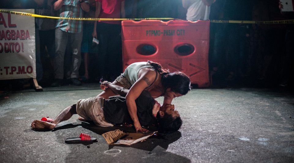 Jennelyn Olaires, 26, cradles the body of her partner, who was killed and left with a sign proclaiming...