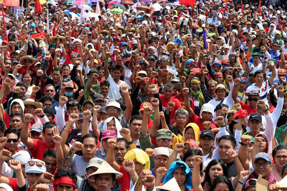 Philippine President Rodrigo Duterte supporters clench their fists during a