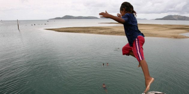 (AUSTRALIA & NEW ZEALAND OUT) Local children fill in their spare time by jumping off the pier on Palm...