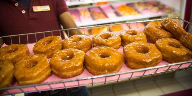 NEW YORK, NY - NOVEMBER 03: A Dunkin' Donuts employee displays a fresh tray of 'croissant doughnuts'...