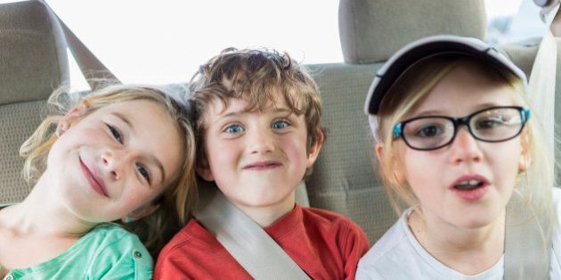 Caucasian children smiling in back seat of