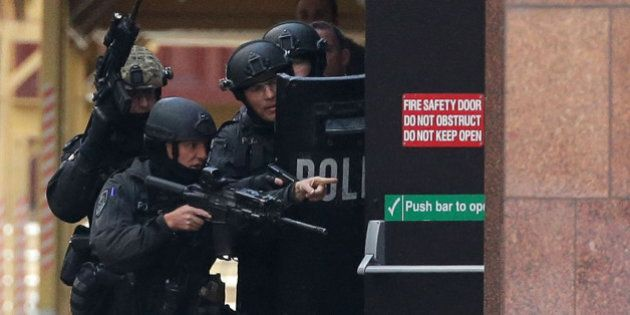 SYDNEY, AUSTRALIA - DECEMBER 15:  Armed police are seen outside the Lindt Cafe, Martin Place on December 15, 2014 in Sydney, Australia.  Police attend a hostage situation at Lindt Cafe in Martin Place.  (Photo by Mark Metcalfe/Getty Images)