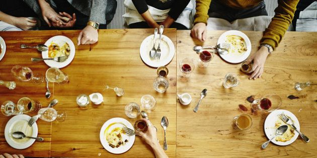 Overhead view of group of friends finishing dessert at table in restaurant