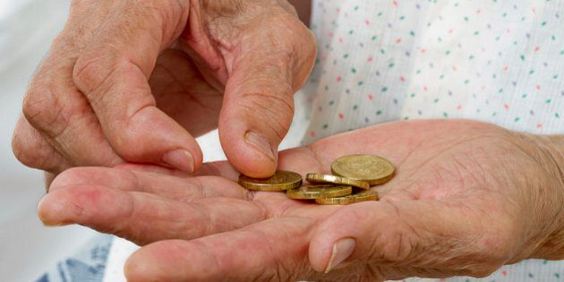 Hands of an old woman with five coins