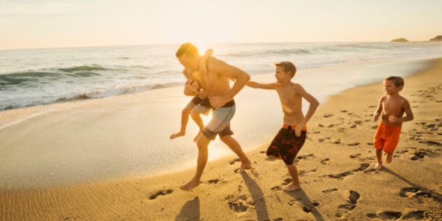 USA, California, Laguna Beach, Father playing football on beach with his three sons (6-7, 10-11,