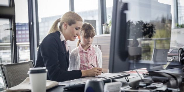 A modern working woman is visited by her daughter at work Horizontal