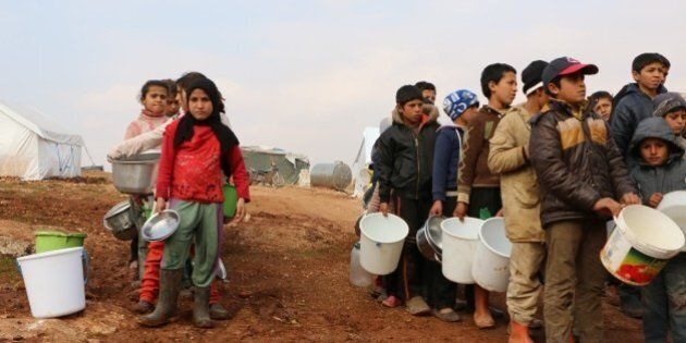 ALEPPO, SYRIA - JANUARY 31: Turkmen children carry wait for food distribution at al-Ra'ee camp, southern...