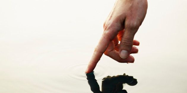Finger touching surface of water