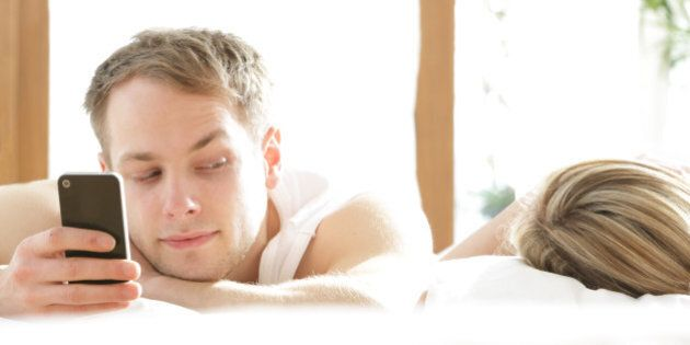 Man with phone in bed, looking at woman